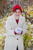 Jonge vrouw die pret met sneeuw op de winterdag heeft Royalty-vrije Stock Afbeeldingen