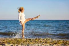 Jonge vrouw die pret op strand hebben stock foto