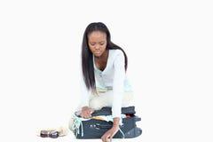 Jonge vrouw die problemen heeft die haar koffer sluiten royalty-vrije stock afbeeldingen