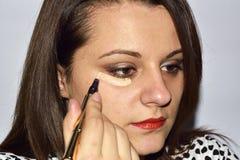 Jonge vrouw die professionele make-up krijgen bij make-upkunstenaar Royalty-vrije Stock Afbeeldingen