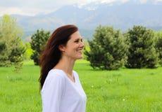 Jonge vrouw die in profiel in de bergen lachen Royalty-vrije Stock Fotografie