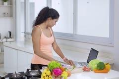 Jonge vrouw die recepten op laptop bekijken royalty-vrije stock afbeelding