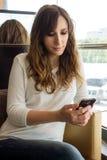 Jonge vrouw die in restaurant wachten die haar smartphone gebruiken Stock Foto's