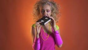 Jonge vrouw die in retro kleren met oude videocassette spelen stock video