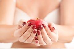 Jonge vrouw die rode appel in hand houden Meisje met rode appel in Ha Stock Afbeeldingen