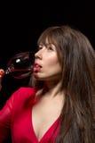 Jonge vrouw die rode wijn van een glas drinken stock foto's