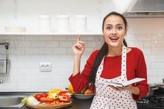 Jonge vrouw die romantisch diner koken die thuis culinair boek houden stock fotografie