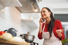 Jonge vrouw die romantisch diner thuis telefoongesprek koken royalty-vrije stock foto
