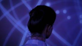 Jonge vrouw die rond moderne immersive tentoonstelling bekijken stock video