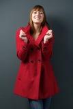 Jonge vrouw die in rood de winterjasje glimlachen royalty-vrije stock afbeelding
