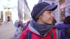 Jonge vrouw die in rood jasje en grijs GLB op de straat lopen stock footage