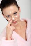 Jonge vrouw die in roze badjas een room op haar neus, wangen en voorhoofd toepassen Stock Afbeeldingen