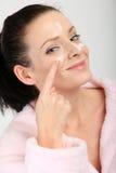 Jonge vrouw die in roze badjas een room op haar neus, wangen en voorhoofd toepassen Royalty-vrije Stock Afbeeldingen