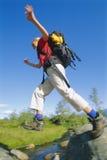 Jonge vrouw die rugzak draagt die over rivier springt Stock Afbeelding