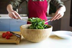 Jonge vrouw die salade in de keuken voorbereiden Stock Foto