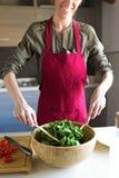Jonge vrouw die salade in de keuken voorbereiden Stock Afbeelding