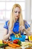 jonge vrouw die salade in keuken mengt Royalty-vrije Stock Fotografie