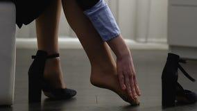 Jonge vrouw die schoenen opstijgen die en benen masseren, na de hele dag gang worden vermoeid stock video