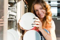 Jonge vrouw die schotels in de afwasmachine zetten royalty-vrije stock fotografie