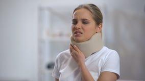 Jonge vrouw die in schuim cervicale kraag scherpe pijn in hals voelen, traumaresultaat stock video