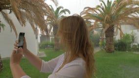 Jonge vrouw die selfie op regenachtige dag nemen stock video