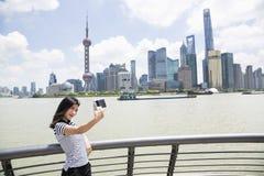 Jonge vrouw die selfie terwijl status door te omheinen tegen Pudong-horizon nemen stock afbeelding