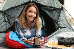 Jonge vrouw die in slaapzak met mok buiten kijken royalty-vrije stock fotografie