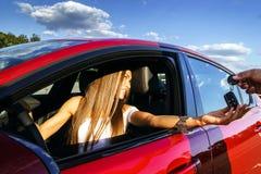 Jonge vrouw die sleutels van nieuwe auto nemen Royalty-vrije Stock Foto