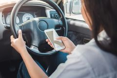 Jonge vrouw die smartphone met behulp van terwijl het drijven van een auto royalty-vrije stock fotografie