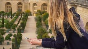 Jonge vrouw die smartphone met de achtergrond van Versailles in langzame motie gebruiken stock video