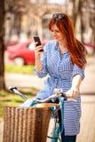 Jonge vrouw die smartphone met het berijden van fiets in stad gebruiken Stock Foto's
