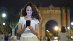Jonge vrouw die in smartphone tegen oriëntatiepunt bij nacht doorbladeren, Barcelona stock footage