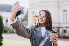 Jonge vrouw die of smartphone texting gebruiken stock afbeelding