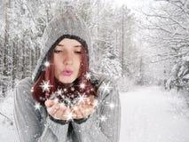 Jonge vrouw die smowflakes in de winterlandschap blaast stock afbeelding