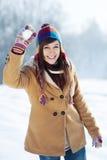 Jonge vrouw die sneeuwbal werpt Stock Afbeelding