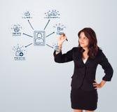 Vrouw die sociale netwerkpictogrammen trekken op whiteboard stock afbeeldingen