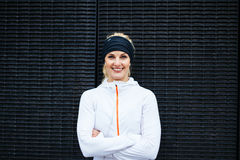 Jonge vrouw die in sportkleding camera het glimlachen bekijken royalty-vrije stock foto's