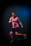 Jonge vrouw die stapoefeningen in de gymnastiek doen Stock Afbeeldingen