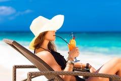 Jonge vrouw die in strohoed bij het tropische strand en enjoyi leggen Royalty-vrije Stock Afbeelding
