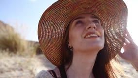 Jonge vrouw die strohoed het ontspannen op het strand dragen stock footage