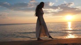 Jonge vrouw die in sundress op het strand bij zonsondergang lopen stock video