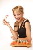 Jonge vrouw die sushi met eetstokjes eten stock foto