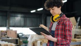 Jonge vrouw die tablet in houten workshop gebruiken die rond en wat betreft het scherm kijken stock video