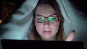 Jonge vrouw die tablet op het bed gebruiken vóór zij slaap bij nacht Mobiel verslaafdenconcept stock footage