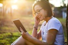 Jonge vrouw die tablet in park gebruiken stock afbeelding