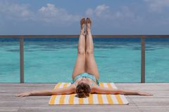 Jonge vrouw die tan op een terras nemen Duidelijk blauw water als achtergrond stock afbeelding