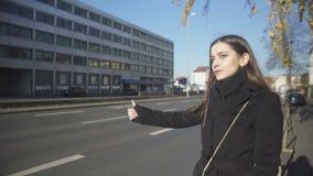 Jonge vrouw die taxi op straat in ochtend, laat voor het werk, lift halen stock video