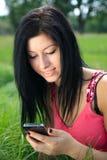 Jonge vrouw die telefoon en het glimlachen bekijkt royalty-vrije stock fotografie
