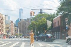 Jonge vrouw die telefoon in straat op achtergrond van taxi kijken royalty-vrije stock foto's