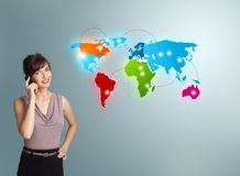 Jonge vrouw die telefoongesprek met kleurrijke wereldkaart maken Royalty-vrije Stock Afbeelding